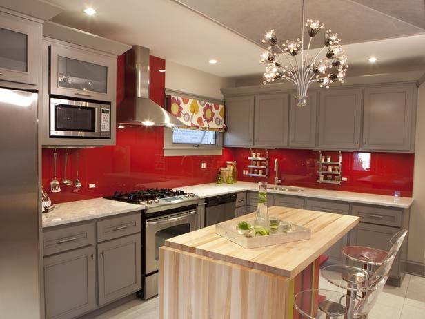Sleek and Contemporary: Meg brings the kitchen back into this century with slate-hued cabinetry, a high ceiling and a fun and funky light fixture. Glass panels atop the bold red walls give the space added shine and make them easy to keep clean, too.