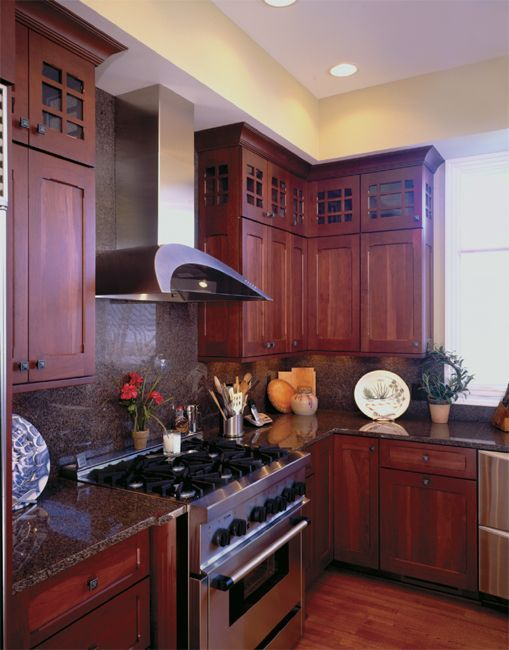 G Shaped Kitchen Cream Cabinets With Black Appliances And Countertops