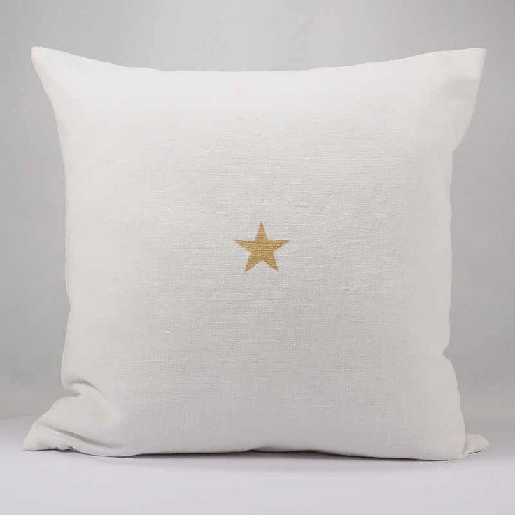 Un joli coussin en drap ancien blanc, avec son étoile dorée.