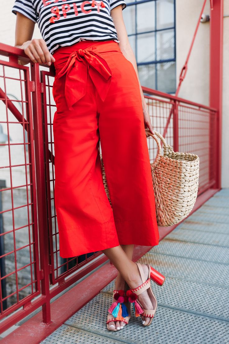 3 easy tricks fashion bloggers like Christine Andrew from Hello Fashion use to put together cute 2017 summer outfits daily, how to layer, pick a color palette, the 3rd piece, how to accessorize and how to pick wardrobe accent colors, red outfit, striped tee, red stripes, pom pom sandals, straw bag, wide leg pants, culottes