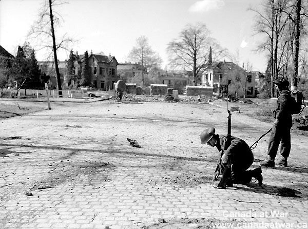 The Netherlands - Members of North Shore Regiment (N.S.r.) hunting and removing mines on approach to destroyed bridge. Zutphen, The Netherlands, 7 April 1945.