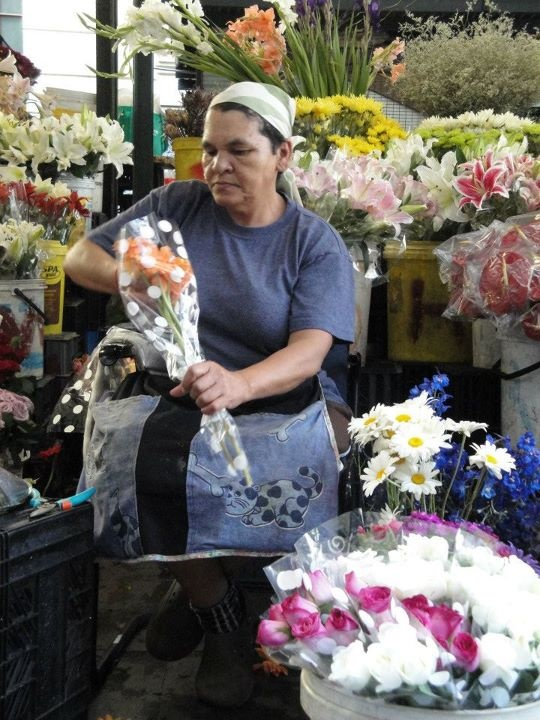 One of the flower-sellers packaging gerberas for a customer at the flower market in Adderley Street