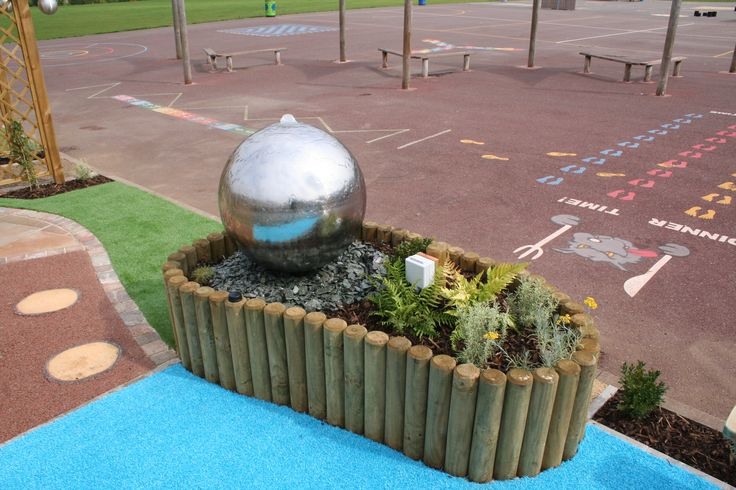 Water feature and raised planting. The children love touching the water and turning the feature on and off.