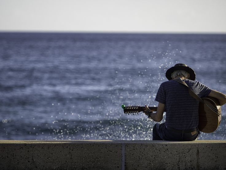 Slack Key by the Sea - As the afternoon turns to evening, a man finds a comfortable spot on a rock wall by the ocean to play a few Hawaiian slack key tunes.  The waves and ocean spray do not appear to interrupt his medley. Kaka'ako Waterfront Park. Honolulu, Hawaii. 2016.