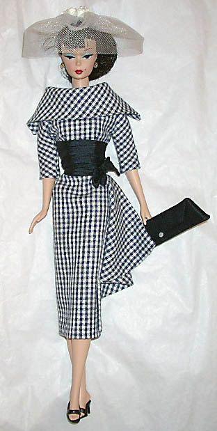 Day dress in navy cotton checks, navy silk waistline, veil with white rosebuds, silk envelope.
