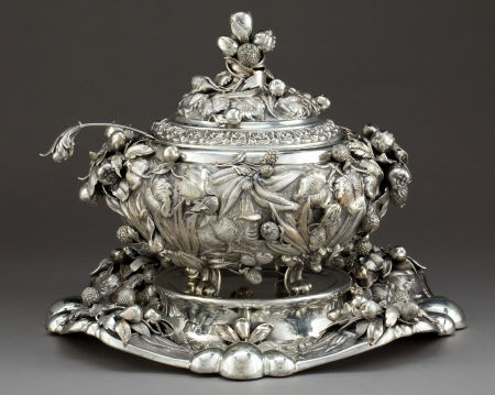 The covered tureen of pomegranates and various fruits and vines on four scrolled feet; ladle with acanthus leaf and pear and terminal end, on tray with undulating rim with similar decoration, raised, round center for tureen. Italian ca 1970