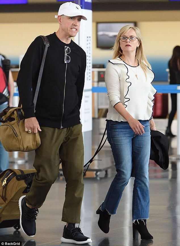 Partner in crime: Reese Witherspoon was spotted with husband Jim Toth after jetting into New York on Sunday