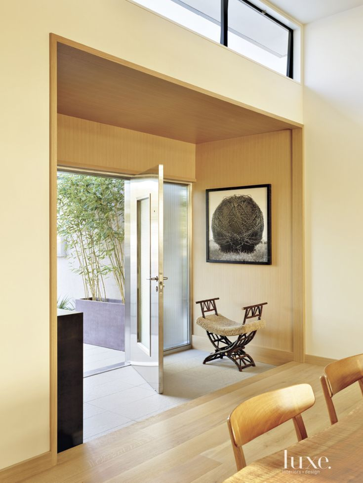 Erik Hughes, co-owner of De Sousa Hughes, and his wife, architect Lorissa Kimm, renovated their 1940s Corte Madera house with a modern feel reflecting their lifestyle and heritages. A custom stainless-steel entry door by Neoporte Modern Door opens to the foyer.