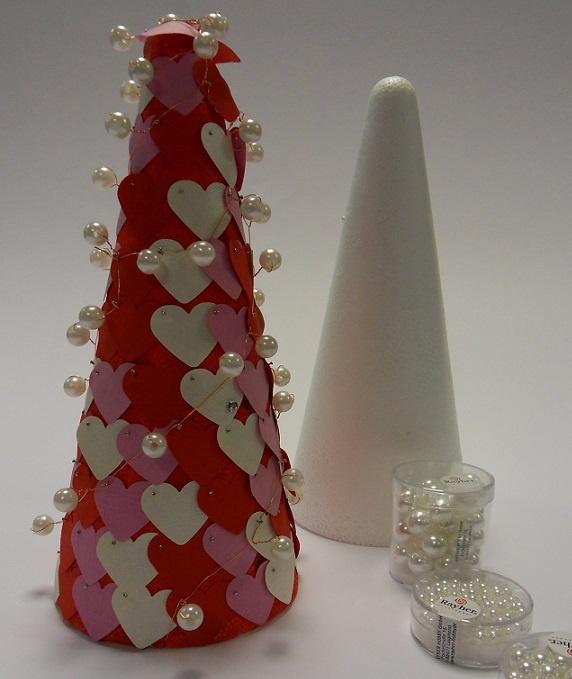 Neem een piepschuim kegel, verf deze met acrylverf in rood. Met een pons stans je hartjes uit papier.  Met spelden prik je de harten in het piepschuim. Rijg kralen aan metaaldraad en drapeer die om de spelden heen.