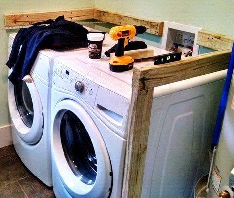 Kaufen Sie Holz und erstellen Sie mit Holzschrauben einen Rahmen um die Waschmaschine und den Trockner