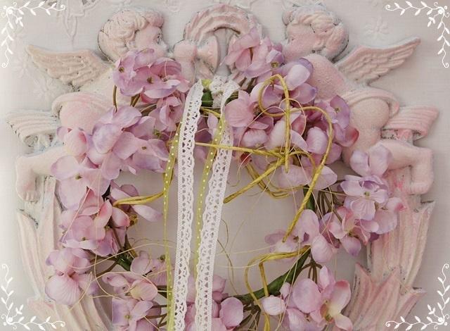 Kraftvoll und mit dicken Pausbacken blasen die beiden Engelchen in ihre Posaunen.  Ein duftiger Blütenkranz aus Hortensien mit Spitzenbändchen häng...