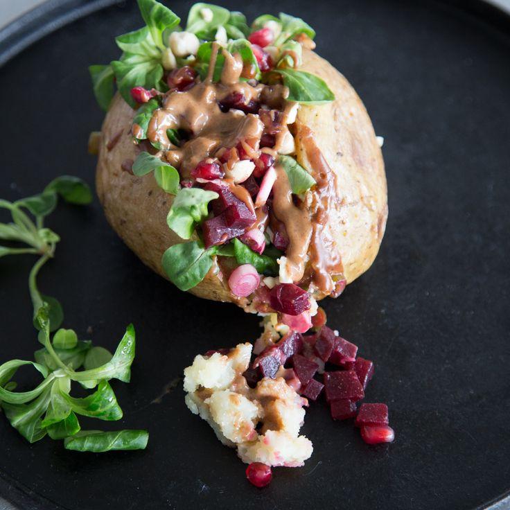 Farbenfrohe Ofenkartoffel: Sonnengelbe Kartoffel trifft auf dunkelrote Bete und knackig grünen Feldsalat. Mandelmus gibt der veganen Füllung den Kick.
