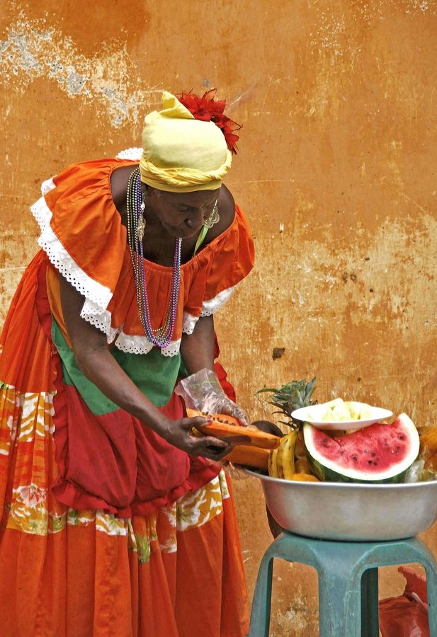 This woman, in her elegant, colorful caribbean dress, sells a few slices of fruit in a street of Cartagena, Colombia.......... by armando cuéllar