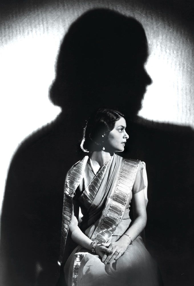 Maharani Gayatri Devi of Jaiopur (1919-2009) c. 1945 The mid-twentieth century saw several photographers innovating with lighting techniques to create more artistic photographs of their patrons. The seated Maharani is lit with artificial light from the front, creating a silhouette on the cloth backdrop behind her.