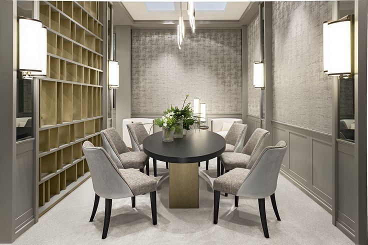 The large elliptic Tao table dominates the dining area. Comprising a wooden top and a base in bronze and wood, it is teamed with two-tone Musa chairs in dove-grey with contrast piping and mahogany legs