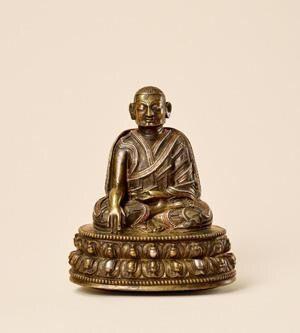 """帕竹噶举上师 创作年代 十四世纪 尺寸 高9cm 估价 400,000 - 600,000 RMB  作品描述 合金铜、嵌红铜、嵌银 来源:朱勒斯.斯彼尓曼(Jules Speelman)珍藏 噶举派(Kagyu School)为藏传佛教四大教派之一,由译师玛尔巴(Marpa)及其弟子米拉日巴(Milarepa)于十一世纪由印度带入西藏,其主要教义出自大成就者底洛巴(Tilopa)的观想体系。噶举派在传承过程中发展出多个分支,一般称为「四大传承、八小传承」,是藏传佛教中分支最多的教派。修行者在修习教法的过程中需得到高僧指导,并奉之为上师,由于弟子和信众尊崇「视师为佛」的传统,往往会依上师容貌制作造像并供奉,形象多数写实生动。 帕竹噶举(Pagdru Kagyu),为噶举派四大分支之一塔波噶举(Dagpo Kagyu)发展出的支派之一,创始人帕木竹巴(Pagmodrupa 1110-1170)为塔波拉杰(Dagpo Lharje 1079-1153)弟子,塔波拉杰对帕木竹巴特别传授了很多密法,并传其""""俱生和合法""""大印法门,此后,帕木竹巴即以塔波拉杰为根本上师。…"""