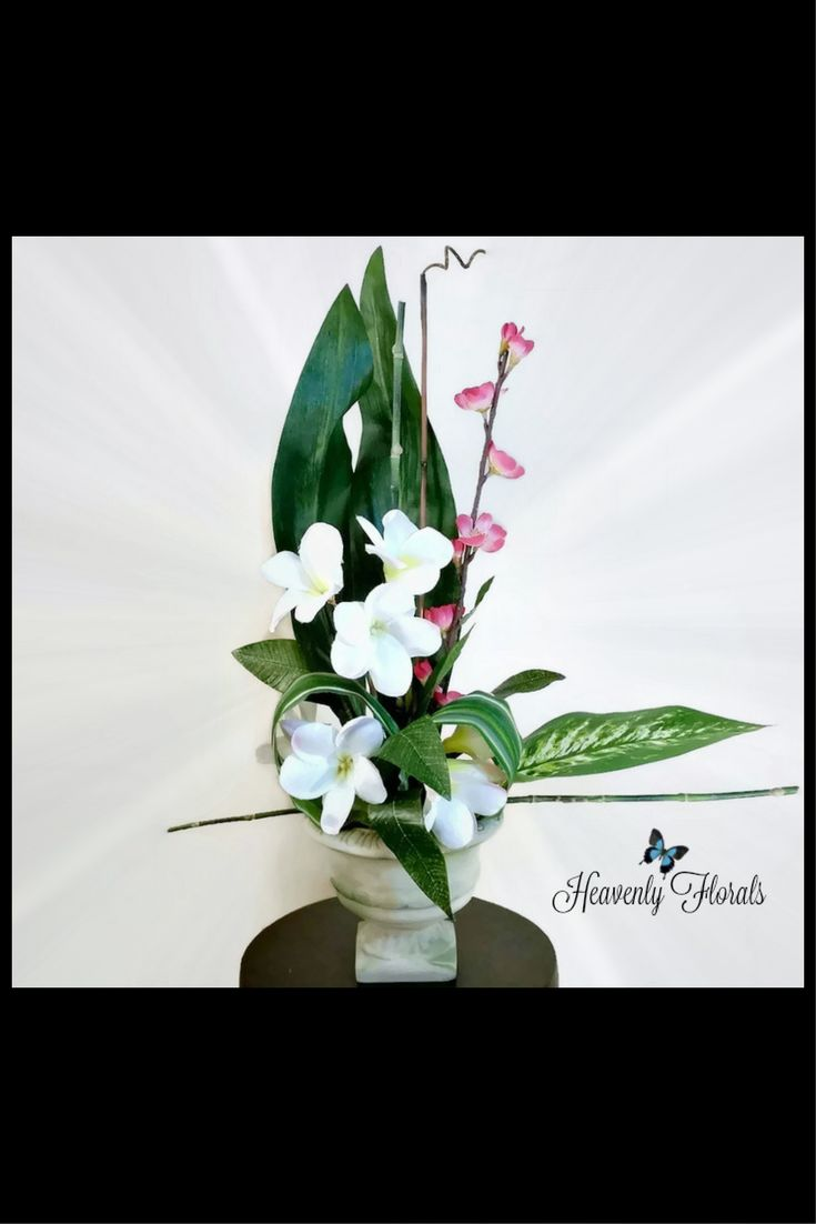 Visit the tropics with this small modern design of plumeria and artistically arranged leaves.