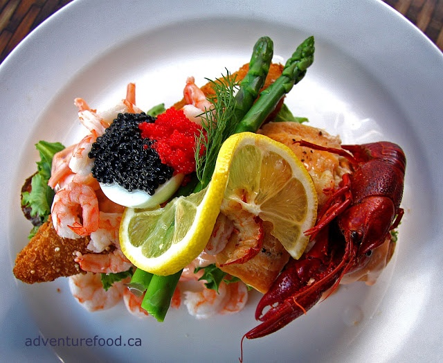 """Stjerneskud is a popular type of smørrebrød in Denmark. Various types of seafood are piled high on a piece of french bread with egg, asparagus and Marie Rose sauce to create an open faced sandwich. """"Sterneskud"""" means shooting star in Danish."""