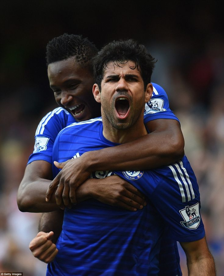 Costa is embraced by John Obi Mikel after scoring his goal against the Gunners
