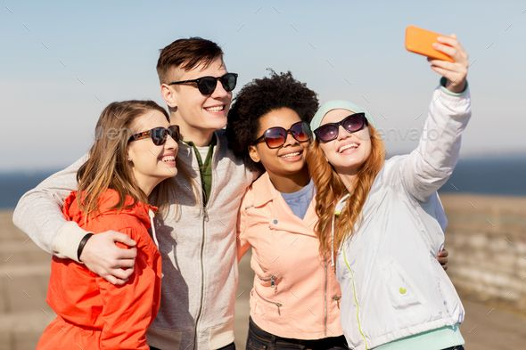 happy friends taking selfie by smartphone outdoors by dolgachov on PhotoDune. people, friendship and technology concept ¨C group of smiling teenage friends taking selfie with smartphone outdoors