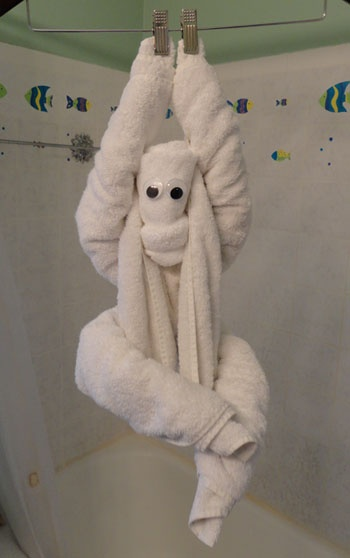 Cute towel origami monkey hanging from a coat hanger. From http://foldingmagic.com . Uses one bath towel and one washcloth.