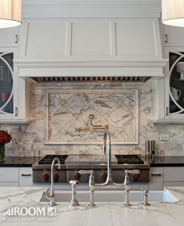 In Hawthorn Woods, IL, a range hood blends seamlessly with the cabinetry, topping a laser-cut backsplash and keeping consistent with the clean, white theme.