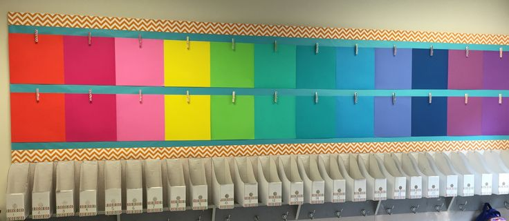 Student work display using colored scrapbook paper and colored clothespins.  The student mailboxes below are Ikea book boxes.