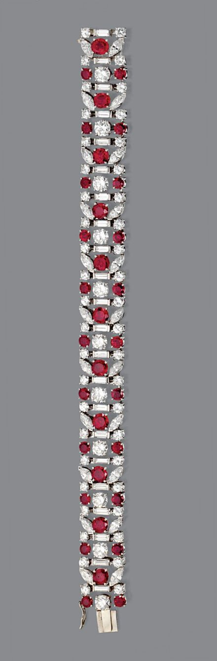 RUBY AND DIAMOND BRACELET, TIFFANY & CO., CIRCA 1950.  The flexible band decorated in a stylized floral motif, set with 55 round diamonds weighing approximately 10.00 carats, 22 marquise-shaped diamonds weighing approximately 4.00 carats, 22 baguette diamonds weighing approximately 2.00 carats and 33 round rubies, mounted in platinum, length 6¾ inches, signed Tiffany & Co. With signed box.