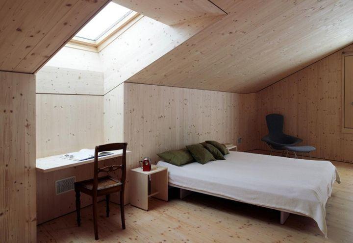 Pavimento e rivestimenti in abete rosso per la seconda camera da letto posta sottotetto. Gli architetti di Hurst Song hanno ideato una piccola scrivania a ribalta sotto alla finestra. Sedia vintage, eredità familiare dei proprietari