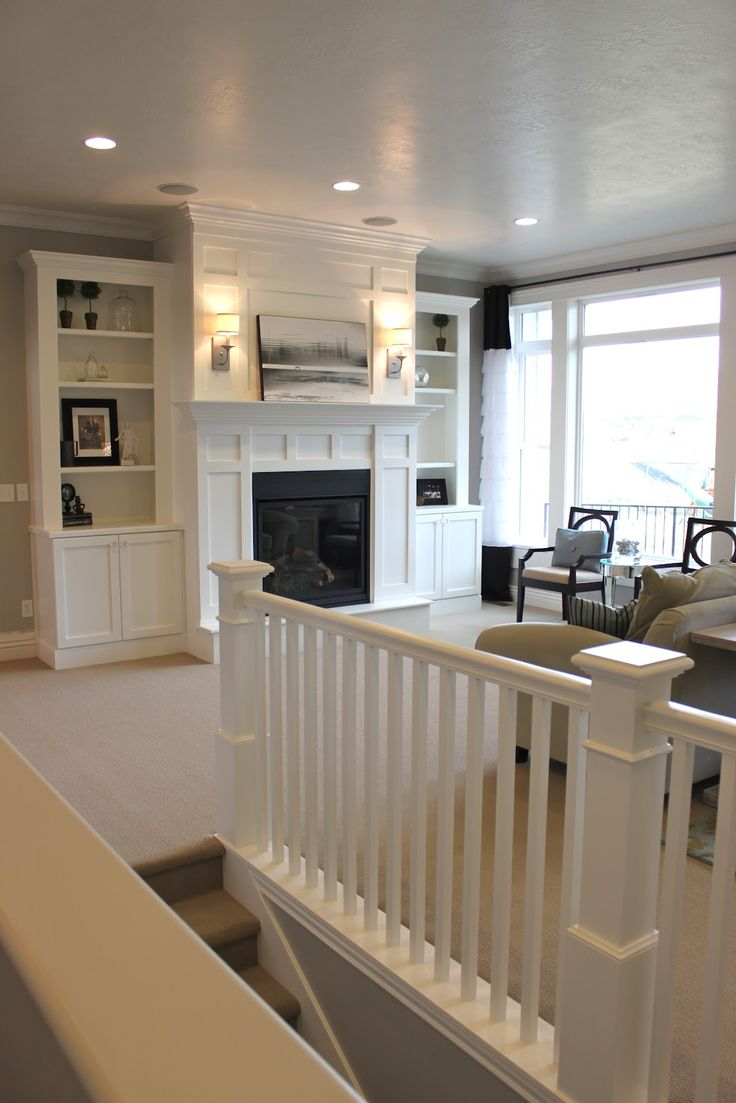 All white built-ins, fireplace, and stairs.
