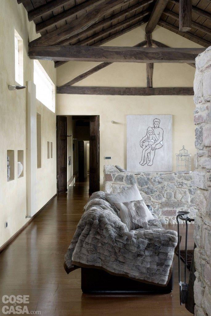 In soggiorno il passaggio verso la zona notte è scandito da una serie di nicchie ricavate nella parete esterna, sfruttando lo spessore di 60 centimetri. All'interno, vasi e oggetti decorativi