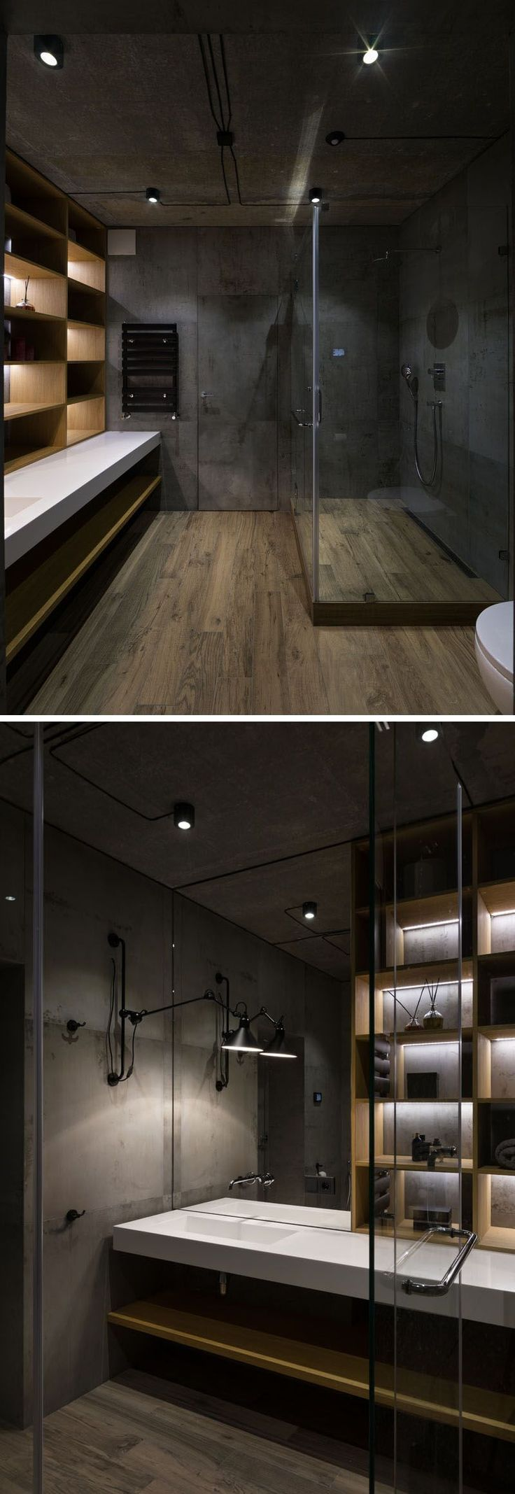 Wood flooring and concrete walls add an industrial touch to this bathroom, while the glass shower surround allows light to pass through. A section of the wall is made up of wood shelves with hidden lighting.