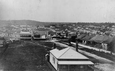 #83AS The 'new chums' were forced to camp out in a valley north of Brisbane near Bowen Hills, and the area slowly became a settlement in its own right. It became known as Fortitude Valley, named after the ship, but also symbolic of the main characteristic of the settlers. photograph of the area from a bit later, around 1882, when little workers' cottages had started to pop up.