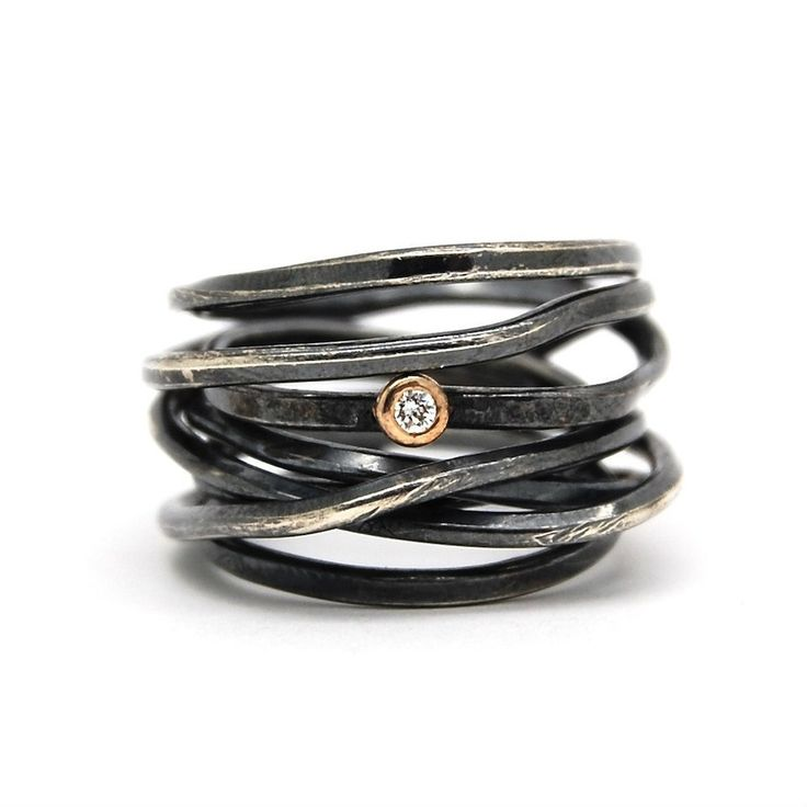 Visibly Interesting: Oxidized Sterling Silver wrapped ring with a conflict-free Diamond in an 18K Yellow Gold setting. Each Bound Ring is one of a kind. The material is shaped by the artist's hand and can display slightly different shapes. The ring can be slightly altered by gently splaying the layers of wire apart or pushing them closer together. The ring was handcrafted by Poppyor, who brings an organic originality to every piece.