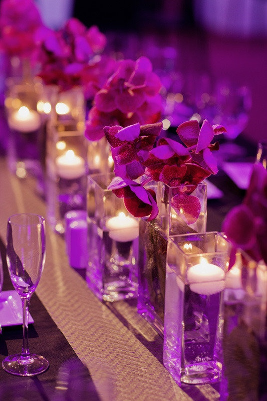 Orchids and purple uplighting. @Tiffany Marie