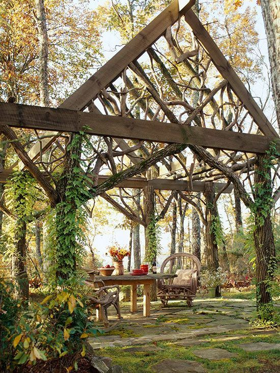 This wooden structure does a great job of blending into it's natural surroundings while still establishing the space as an outdoor room. A wooden table and chairs made out of twisted branches continue the nature-inspired look. Vines growing up the structure's supporting beams help to further conceal the piece./