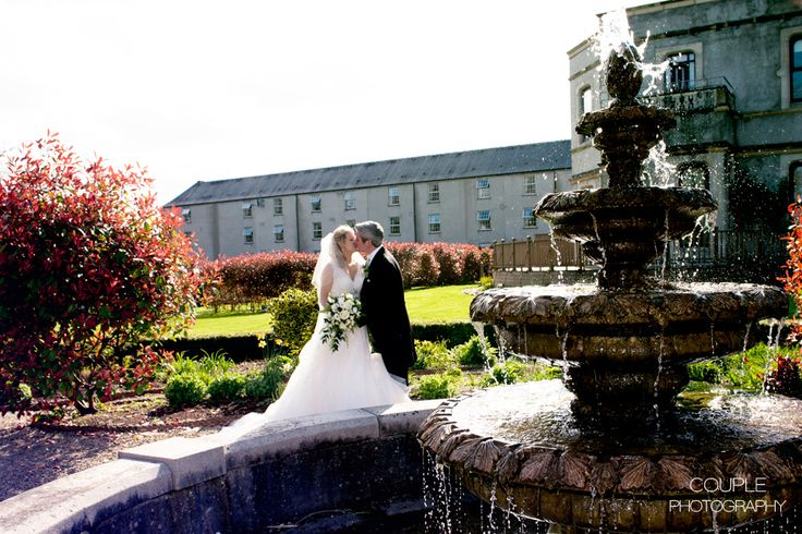 The happy couple have a kiss at the fountain at Killashee. Weddings at Killashee House Hotel photographed by Couple Photography.