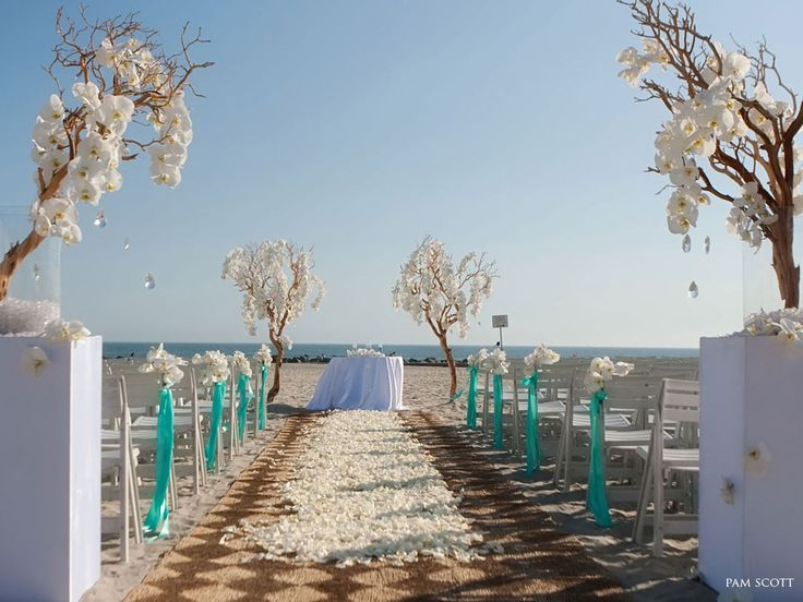 Beach wedding with style: bamboo or rattan aisle runner, sprinkled with petals. Turquoise aisle ribbons with flower heads. Branches with flowers at front and back, with tear-drop 'gems' hanging free.