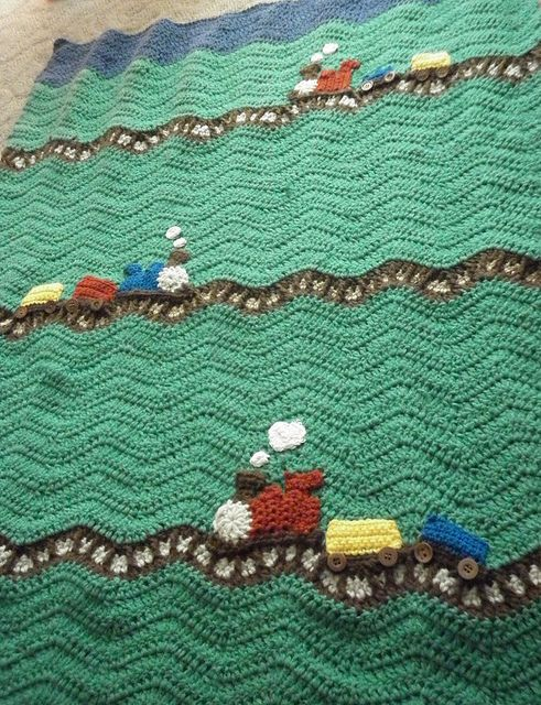 This is really a cute Train Blanket. A wavy afghan the tracks are easy enough sc under the white/then on top of the white would be sc and long dc to the brown 2 rows down. Trains look easy enough. Wheels are buttons.