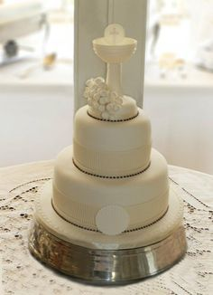 Three tier communion cake with decorative chalice.