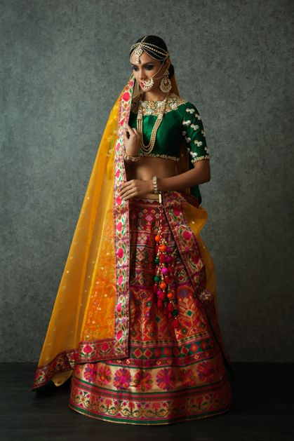 Sangeet Lehengas - Multi-colored Lehenga with Green Blouse | WedMeGood | Multi Colored Lehenga with Green Emerald Blouse with Embroidered Sleeves, Yellow Dupatta, Pearl and Gold Mang Tikka, Maatha Patti and Nath #wedmegood #lehengas #indianwedding #indianbride #choli Outfit by: Benzer