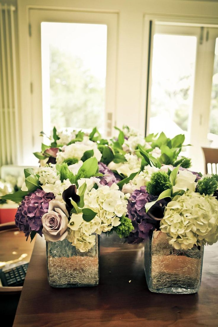 Vermont wedding flowers: Hydrangeas, roses, and calla lilies in elegant, simple vases.