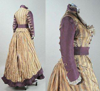 Платье 1870-х годов из шёлковой тафты. Лиф с квадратным вырезом, отложной воротник по внутреннему краю отделан кружевом. Застёжка на круглые пуговицы, обтянутые фиолетовой тафтой. Длинные рукава с необычной отделкой, напоминающей погончики - влияние военного костюма. Юбка состоит из двух частей - верхнее полотнище из полосатого шёлка приоткрывает нижнее, отделанное горизонтальными рядами оборок из плиссированной тафты.