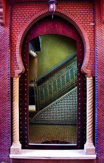 Very pretty image showing a Moorish arch, as well as Moroccan mosaic zellij tiling at the base of the stairs and a green tadelakt (special Moroccan surface treatment) wall.