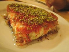 "Knafeh... This is arguably the most famous Middle Eastern dessert. This is the Middle East's version of our ""apple pie"", metaphorically speaking. Typically, this dessert is a sweet cheese topped with one of two types of crust-like topping. I prefer the crumbled topping, personally. Then it is topped with pistachios and smothered in a sweet sugar syrup. It is the perfect end to any Middle Eastern meal and served at every major celebration. Absolutely incredible!"