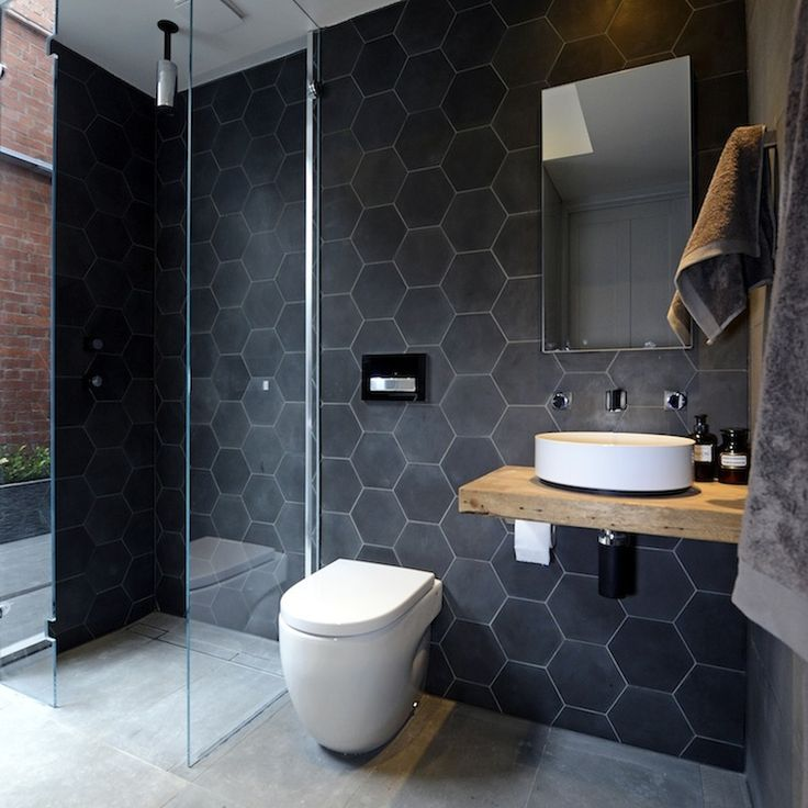 Modern bathroom features a black slate hexagonal tiled accent wall which highlights an open shower with mirrored door adorned with a modern ceiling mount shower head over industrial style concrete shower floors. A modern toilet with wall flush stands beside the shower next to a floating wooden sink console fitted with a round vessel sink below a modern wall mount faucet and simple frameless medicine cabinet.