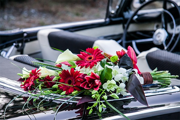 Stunning red lilies, Gerbera, orchids and Calla lilies perched on the back seat of a vintage, convertible Ford Sunliner