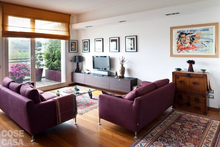 La zona conversazione è pensata come uno spazio ben definito che usufruisce della luce naturale della vetrata affacciata sul balcone. La vicina parete è attrezzata con mobile sospeso e tv a schermo piatto, illuminati dall'alto da due faretti incassati in una struttura in cartongesso aggettante. Le tonalità calde si mescolano con molti arredi di ispirazione orientale, tra cui alcuni tappeti afghani