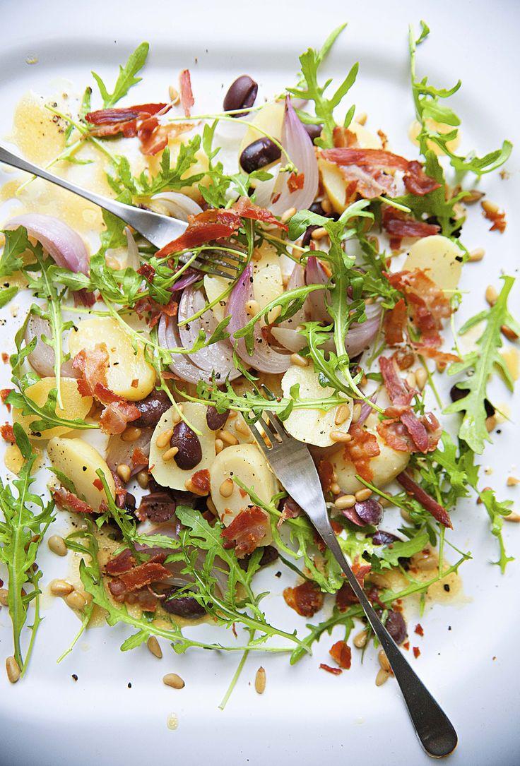 Ensalada de arúgula con cebolla asada, papas, tocino, aceitunas y piñones.