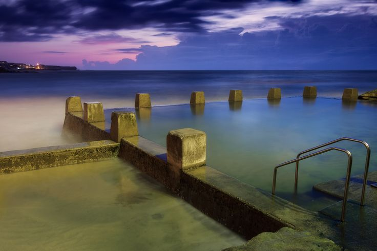 Ross Jones Memorial Pool at Coogee, NSW Australia. Just before sunrise with the storm clouds on the horizon makes for dramatic skies with a pink tinge.